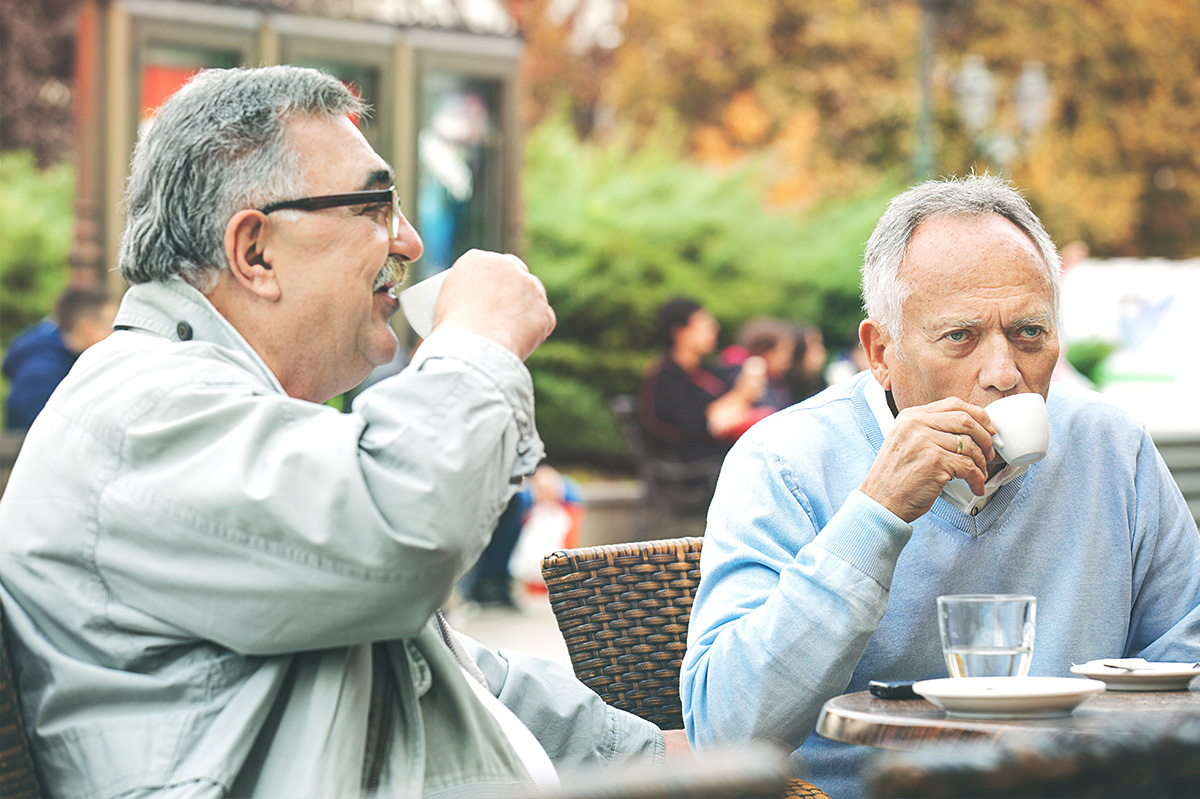 Two older men talking over coffee